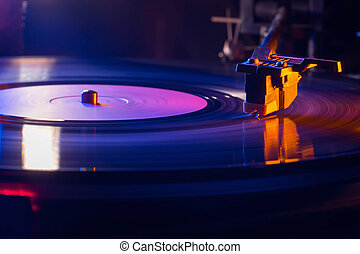 Retro-styled film look of a spinning record vinyl player. Close up. Side view. Colorful movie with neon light