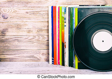 Retro styled image of a collection of old vinyl record lp's with sleeves on a wooden background with Copy space toned
