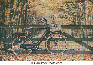 Retro styled image of an electric cargo bicycle in autumn