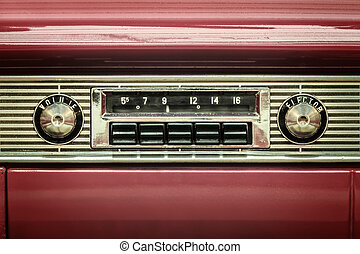 Retro styled image of an old car radio inside a red classic...