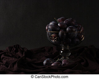 Retro-styled low key still life with plums