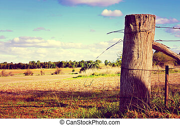 Retro sunset filter style country side scene with old gate post and barb wire. Taken at Barossa Valley, South Australia.