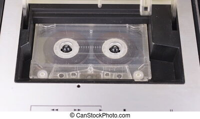 Retro technology. The person stops and ejects the audio tape from the tape recorder. Close-up