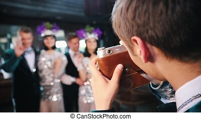 Retro theme party - a man takes a photo of his friends on the retro camera