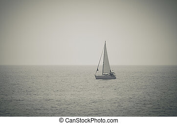 Retro toned picture of yacht sailing on the sea