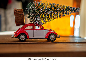 Retro toy car carrying tiny Christmas tree