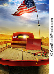 Concept photo of a vintage red vintage pick up truck with American flag waving above against rural dramatic cloudscape