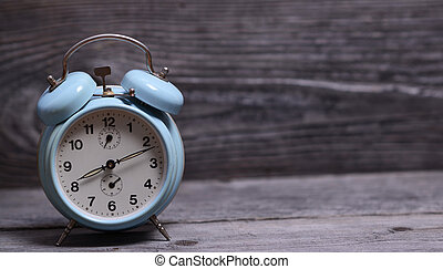 Retro turquoise clock on wooden background