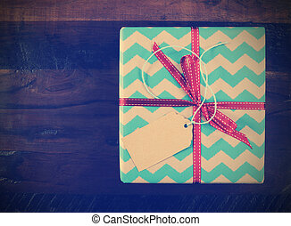 Retro vintage gift box with chevron stripe wrapping on dark recycled wood table.