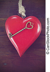 Retro vintage style Happy Valentines Day key to my heart concept with large hanging heart on dark wood background, vertical.