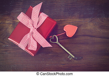 Retro vintage style Happy Valentines Day key to my heart concept with large hanging heart on dark wood background with gift.