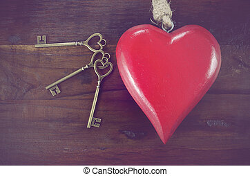 Retro vintage style Happy Valentines Day key to my heart concept with large hanging heart on dark wood background.