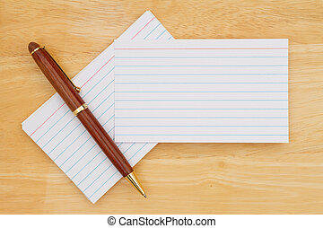 Retro white paper index cards with pen on wood desk