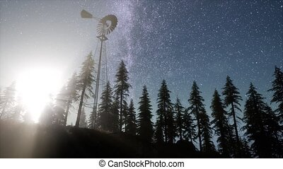 retro windmill in mountain forest with stars. hyperlapse