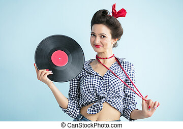 Retro woman in fifties style holds a musical record.