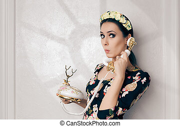 Funny young woman talking on a old embellished telephone