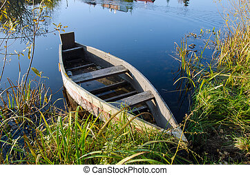 Retro wooden boat on lake shore. water transport