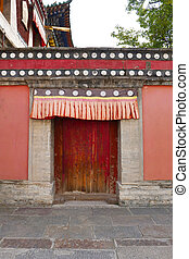 Retro wooden door and wall in Kumbum Monastery, Ta'er Temple a Tibetan Buddhism Monastery in Huangzhong County, Xining Qinghai China.
