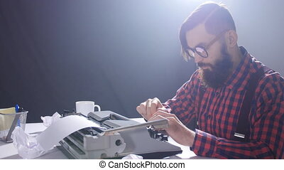 Retro writer concept. Young Bearded stylish man writing on...