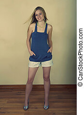 Full length portrait of a charming young woman smiling with long blond hair against wall on wooden floor in retro style