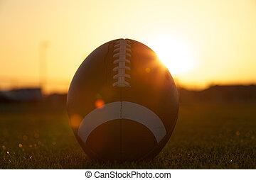 retroilluminato, football americano, a, tramonto