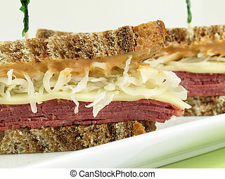 Reuben sandwich with corned beef, melted swiss cheese, sauerkraut, and thousand island dressing on marble rye bread.