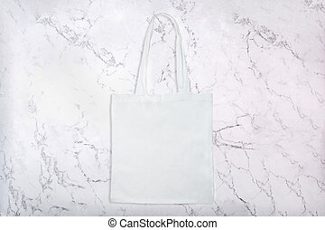 Reusable white fabric bag on white natural marble texture as...