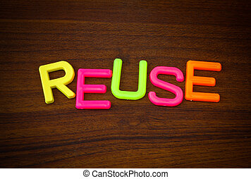 Reuse in colorful toy letters on wood background