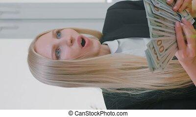 reussite, oui, tenant argent, femme femelle, bureau., paquet, gesture., étonné, mains, célébrer, lieu travail, confection, heureusement, espèces, regarder, lancement, séance, air, moniteur, élégant, blonds