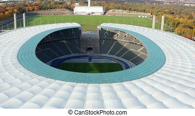 Revealing Establishing Shot of Empty Stadium showing green Soccer Football field in Berlin, Germany, Aerial tilt down dolly forward wide view
