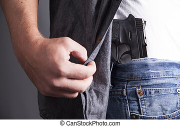 Revealing Firearm - A man reveals a concealed pistol at his...