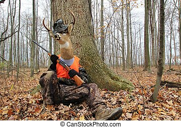 Deer with a shotgun waiting for an elusive hunter to wander by.
