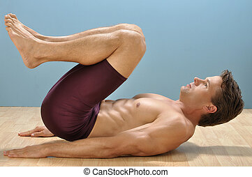 Fit muscular shirtless man performs reverse crunch abdominals exercise on floor