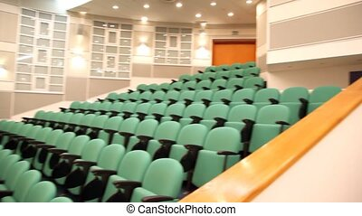 empty green armchairs in lecture hall