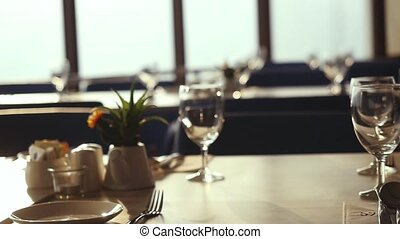 Review hall with decorated table, cutlery and chairs in restaurant decorated for wedding celebration during sunset. slow motion.