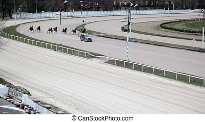 horses with equestrians competing on hippodrome track before...