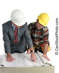 An engineer and a construction foreman reviewing blueprints - isolated