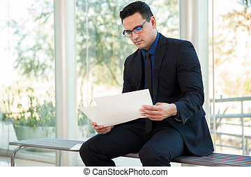Young businessman sitting on a bench and reviewing some documents at work