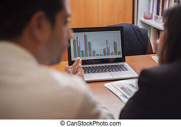 Business colleagues reviewing work results on a laptop
