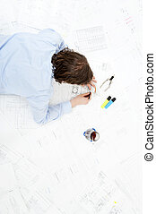 Revising technical drawings - Engineer lying on several...
