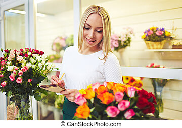 Young florist making notes in notepad during working day in the shop