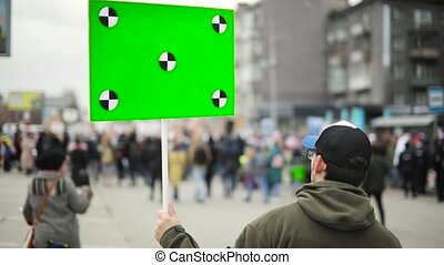 Man holds poster with green screen and walking the street...