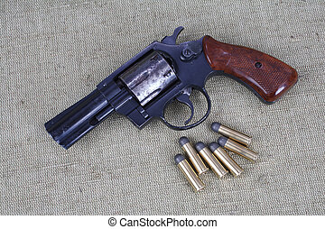 Revolver with ammunition on the canvas background