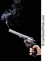 hand holding a revolver with smoking barrel, against black background