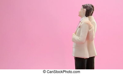 Revolving gay groom cake toppers on pink background