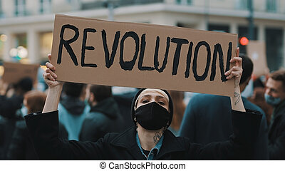 Revoultion concept. Young woman with face mask and banner protesing in the crowd