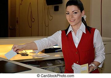 Rezeptionistin bei Zimmervergabe - Hotelfachfrau uebergibt...