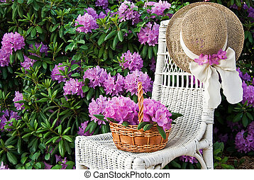 Rhododendron Garden - Basket of flowers and hat on white...