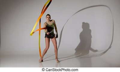 Rhythmic gymnast doing acrobatic moves with the tape. White background