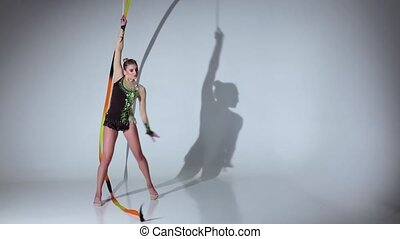 Rhythmic gymnast doing acrobatic moves with the tape. White background. Slow motion